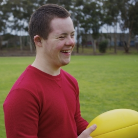 Sixteen-year-old boy smiling while holding football at park